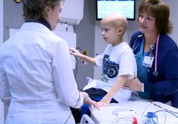 Charlie's mom helps him onto the proton beam therapy couch before treatment.