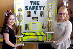 Jadyn Waddle and Kylie Thompson of Heritage Trails Elementary School in Moore Oklahoma display their trophies next to their winning invention: a tornado safety vest.