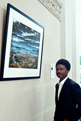 "Fine Art Photographer Diallo Mwathi Jeffery at his photographic work of art ""Bay Sky One"" in the Oakland City Hall Rotunda Gallery"