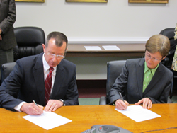 RADM J. Scott Burhoe, President of FUMA (left), and Dr. Debbie L. Sydow, President of Richard Bland College of William and Mary, sign historic partnership agreement.