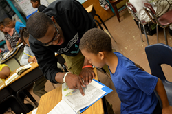 A Howard University student helps a child with a reading exercise at Henry Ford Academy in Detroit (2012).