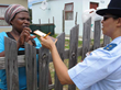 A Plettenberg Bay police officer offers a resident a copy of The Way to Happiness  booklet to help her help her family live a better, happier life.