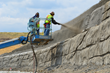 A Hayward Baker nozzleman and pump operator applying shotcrete to a soil nail lift prior to sculpting, behind a housing development in Arvada, CO.