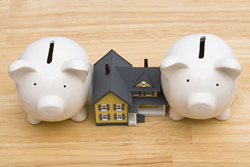 Image credit: <a href='http://www.123rf.com/photo_3323693_home-with-piggy-bank-being-squeezed-by-a-second-mortgage.html'>karenr / 123RF Stock Photo</a>