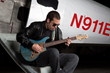 Albert Castiglia sits playing his guitar.