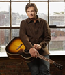 Billy Dean stands in front of a window holding a guitar.