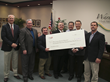 Georgia Power's Richard Highsmith (far right) and James Willis present a large check for energy conservation to Ware County superintendent Mark Mooneyhan (center) as IP UtiliNET's Mitch McGhee (holdin