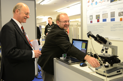 Peter Hartmann, at left, evaluates an entry in the 2012 Photonics Innovation Village. Thirteen projects are competing for the 2014 prizes.
