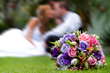 close up on flower bouquet with newlyweds in background