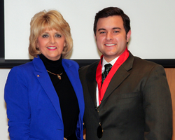 Rose State College President Jeanie Webb presents student Jared Bradley with a bronze medal for his achievement as a Coca-Cola scholar