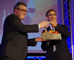 Photonics21 president and JENOPTIK CEO Michael Mertin (L)  presents a symbolic gift of laser-engraved eggs and apples to former  EC Photonics Unit head Thomas Skordas
