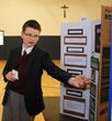 Kamil, an 8th grader at Everest Academy, presents his findings as part of his presentation which earned him 2nd Honors in the Regional Science Fair.