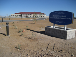 Brackish Groundwater National Desalination Research Facility with sign of building in the front. Desert landscape in front of the building.