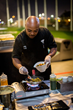 A Topgolf chef at a live cooking station on the tee line at Topgolf Houston North
