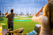 A golfer takes a swing at Topgolf in Spring, TX.