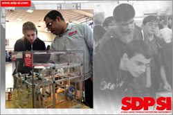 Orville Ashley showing a student a mechanical drive display, showcasing some of the parts that SDP/SI offers and how they can be used in an application.