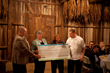 During their 'Seasons on the Farm' dinner, Maryland farmers presented representatives from the Southern Maryland Food Bank with a check for $3,995, proceeds from the purchase of plates and tables, and a silent auction that evening.