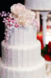 three tier wedding cake with pink accents