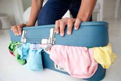 Woman packing over-stuffed suitcase