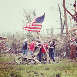 Volunteers from New Life Church form a prayer circle near an American flag in Mayflower, Ark., during clean up efforts following the April 27, 2014 tornado.