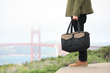 The Outback Duffel—lifestyle shot at Golden Gate Bridge; black ballistic nylon with grizzly leather details