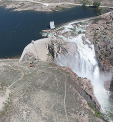 Pathfinder Dam with water spilling over the spillway. Photo taken from helicopter.