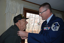A Veteran is honored by a active duty member of the military.