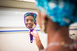 Gisele was given a new dress and headdress by Mercy Ships. She sees herself in the mirror for the first time with her new outfit and new outlook on life after her fistula has been repaired.