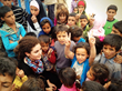 Hazami Barmada pictured with a group of Children in Zaatari camp