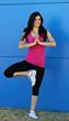 Model Christine Rahman doing a yoga pose wearing a gorgeous pink yoga tank by TerraFrog.