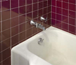 Before - Dingy bathtub that is difficult to clean with dated red tile surround