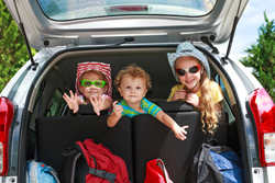 three kids sitting in the back of a car