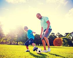 Dad and kid playing football