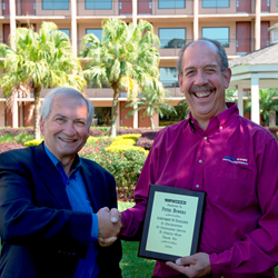 "Peter Bowers (right) receives ""Achievement of Excellence"" award from Stertil-Koni president, Dr. Jean DellAmore."