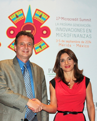 Larry and Elenitza shaking hands in front of a backdrop printed with 17th Microcredit Summit logo