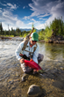 A guest at Natural Retreats Tsaina Lodge hauls in an impressive Sockeye Salmon.