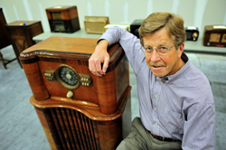 Salt Lake Community College director of media operations Bill Bradford sits next to an antique radio console that will be part of a unique exhibit of antique electronics at SLCC.