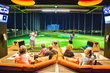 Guests lounging in their hitting bays at Topgolf at Riverwalk