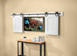 The Horseshoe Rolling Barn Door Hardware shown here is being used to conceal a flat panel TV.