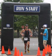 A triathlete crosses the finish line during the Morrison Family YMCA's Adult Tri Ballantyne.