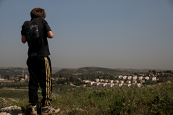 Palestinian child from the West Bank village of Nabi Saleh looks off at the Israeli settlement of Halamish.