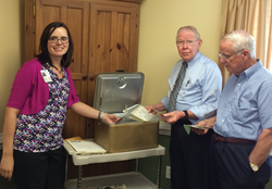 Current and former leadership at Piedmont Crossing sift throught contents in time capsule.