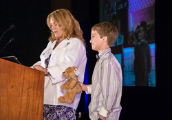 Tracy Schmidt of WellCare and a Family Café board member, speaks to attendees, alongside her son Landon, about her family's experience with his cleft palate. (photo by Gil Williams)