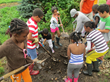Children from Hope Residence turning compost at Abma's Health Barn