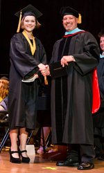 Picture of Commonwealth Connections Academy CEO Maurice Flurie presenting graduate Mackenzie Steudler with her high school diploma.