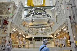 The Orion crew module for Exploration Flight Test-1 is shown in the Final Assembly and System Testing (FAST) Cell, positioned over the service module just prior to mating the two sections together. The integrated crew and service modules will be put throu