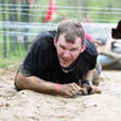"Father Jonathan Meyer crawls beneath barbed wire during the Spartan Race in Laurel on April 27, 2012. The barbed wire challenge will be part of the ""Tame the Terrain"" race in North Vernon on June 22."