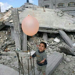 A young boy plays with a balloon next to collapsed buildings in Beit Lahia, Gaza Strip.