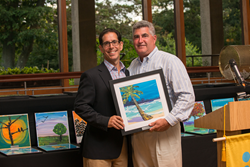JCC President Michael Rosenbaum (right) presents honoree Frank Zuckerbrot with a painting made by a participant of one of the JCC's Alzheimer's programs.