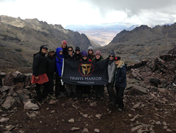 Women at the top of mountain holding Travis Manion Foundation flag.
